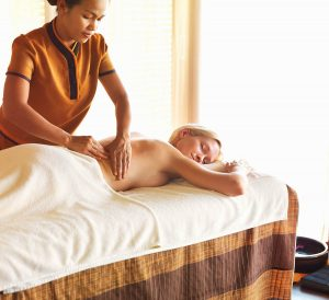 Mixed race masseuse giving relaxing massage to female client at spa